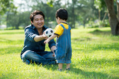 Playing with father. Image of a father giving a ball to his little son on the foreground stock photos