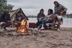 Playing favorite song. Group of young people in casual wear smiling while enjoying beach party near the campfire stock photos
