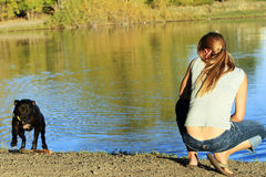 Playing Fetch. A young woman plays fetch with her Pit Bull at a local pond Royalty Free Stock Photo