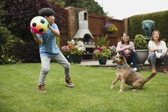 Playing Fetch in the Garden. Little boy is playing fetch in the garden with his pet dog and a ball. His mother and grandmother are watching with a cup of tea royalty free stock image