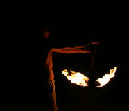 Playing With Fire. Glow from the flame illuminates the fire spinners fit torso Stock Photography