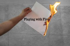 Playing with fire words text on fire with burning paper. In hand stock image