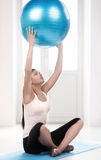 Playing with fitness ball. Beautiful young women exercising at home Royalty Free Stock Photography