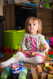 Playing on a floor. 1-2 years old baby girl on a floor with toy cubes, car and other toys Stock Image