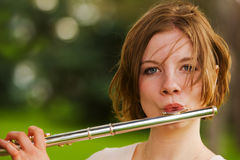 Playing the flute. A pretty teen playing her flute outside Stock Image