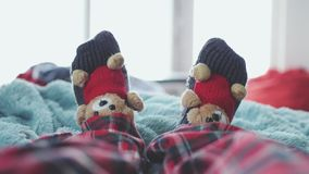 Playing foot at home in bed dressed socks with cute teddy bears and in pajamas against the background of a blurred. Playing foot at home in bed dressed socks stock video