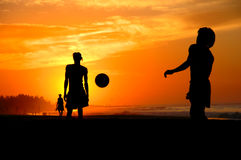 Playing footbal at the sunset on the beach Stock Photography