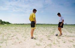 Playing football. Teenagers play football on sands Stock Photo
