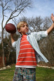 Playing Football. Young cute boy throwing the football Stock Image