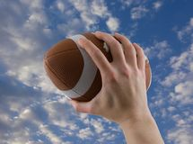 Playing Football. Hand passing or catching a football with cloudy sky background Stock Photo