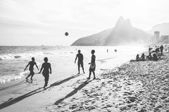 Playing football on the beach stock photography