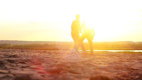 Playing football on beach at sunset, sports students relaxing on beach. Playing football on beach at sunset, sports students relaxing on beach stock video footage