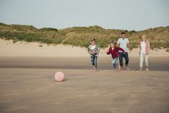 Playing Football on the Beach. Wide angle view of family playing football on the beach Royalty Free Stock Images