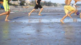 Playing football children on beach polluted by trash and garbage. Kids enjoy in sport on sand. Environmental problem on beach stock footage
