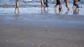 Playing football children on beach polluted by trash and garbage. Kids enjoy in sport on sand. Environmental problem on beach stock video