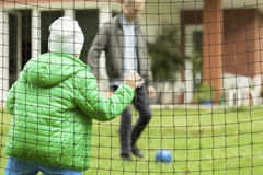 Playing football in a garden Stock Image