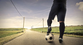 Playing football on a long way Stock Photography