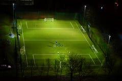 Playing football at night Royalty Free Stock Images