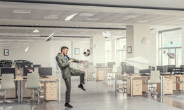 Playing football in office Royalty Free Stock Photography