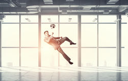 Playing football in office . Mixed media Royalty Free Stock Photography