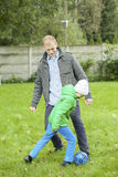 Playing football together with son Royalty Free Stock Photos