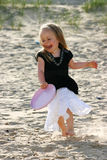 Playing frisbee on a beach. Three years old girl playing with plastic disc on a beach Royalty Free Stock Image