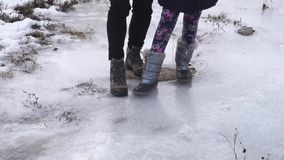 Playing on a frozen creek. Close up stock footage