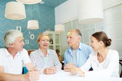 Playing Funny Game with Friends. Cheerful elderly friends playing guessing game while sitting at table with sticky notes on their foreheads, interior of stylish Stock Images