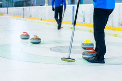 Playing a game of curling. Indoor sport played on ice Stock Photos