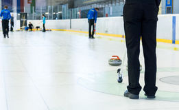 Playing a game of curling. Indoor sport played on ice Stock Photo