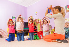 Playing game and group of kids show home with hand Royalty Free Stock Images