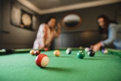 Playing A Game of Pool. Focus on foreground of a red striped pool ball. In the background there are two mid adult friends playing a game of pool in a games room stock photography