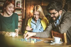 Playing game together. Friends at cafe. Three young people playing leisure game at cafe. Small group people Royalty Free Stock Photos