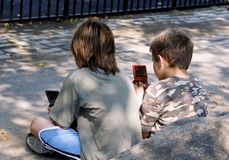 Playing games. Two boys playing pocket games stock photos