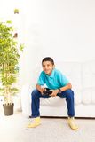 Playing games at home. Happy black 10 years old boy playing video games holding game controller sitting on the white sofa in living room Royalty Free Stock Image