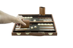 Playing Games Series - Woman's Arm Playing Backgammon. A woman's arm playing backgammon by throwing the die on the backgammon board with her left hand. Isolated stock photo
