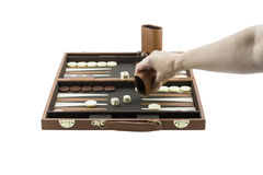 Playing Games Series - Woman's Arm Playing Backgammon. A woman's arm playing backgammon by throwing the die on the backgammon board with her righ hand. Isolated stock images