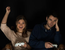 Playing games. Young couple, men and women play computer games sitting in dark room in front of tv or monitor, holding game controllers in their hands Royalty Free Stock Photo