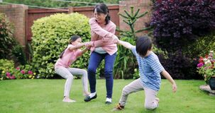 Playing in the Garden with Grandmother. Two children are playing in the garden in summer with their grandmother, pulling her by each arm stock footage