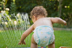 Playing with garden sprinkler. Baby boy trying to catch water from a garden sprinkler stock images