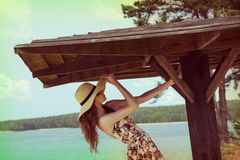 Playing girl ner lake with summer hat Stock Photos