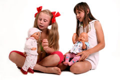 Playing girls. Two girls playing with dolls Royalty Free Stock Images