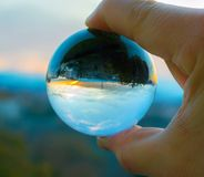 Playing with glass sphere. Catching sunrise in a sphere Royalty Free Stock Image