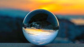 Playing with glass sphere. Catching sunrise in a sphere. Playing with glass sphere. Catching sunrise from my balcony . Photo was taken in Rijeka, Croatia Stock Images