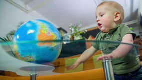 Playing with a globe. Young boy standing next to glass table in a living room and spinning the globe with his hand slow motion footage stock footage