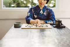 Playing Go board game. Japanese girl drinking tea and playing Go board game Stock Photography