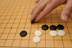 Playing go game. A hand putting go stone to the board Royalty Free Stock Photography