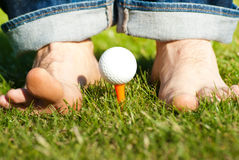 Playing golf barefoot Stock Images