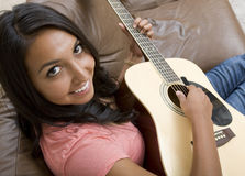 Playing Guitar. Attractive young lady playing an acoustic guitar on her sofa stock images