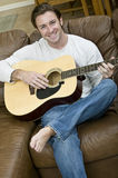 Playing Guitar. An attractive man playing the acoustic guitar Royalty Free Stock Images